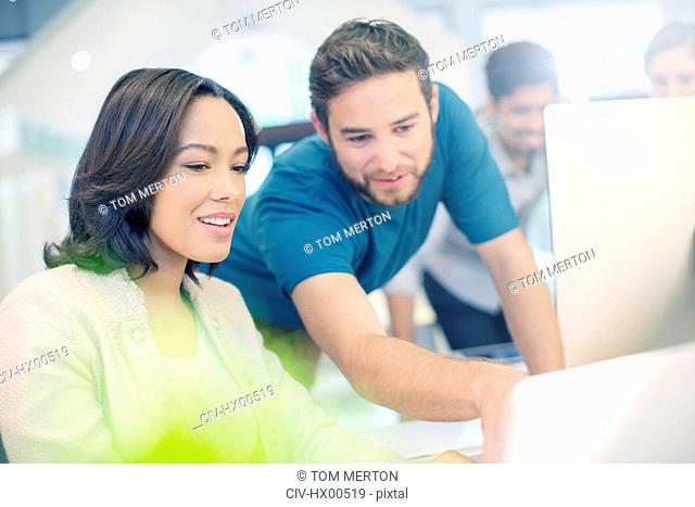 Creative business people using laptop in office