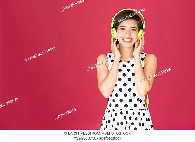 Beautiful young multiracial woman laughing and listening to music with green headphones.1015