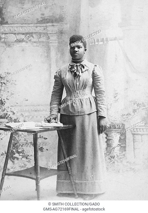 A full length photographic portrait of an unidentified woman, she is wearing a long sleeve blouse with a bow at the neck line and a floor length skirt