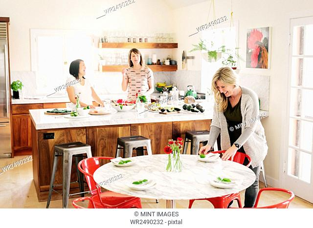 Three women in a kitchen preparing lunch