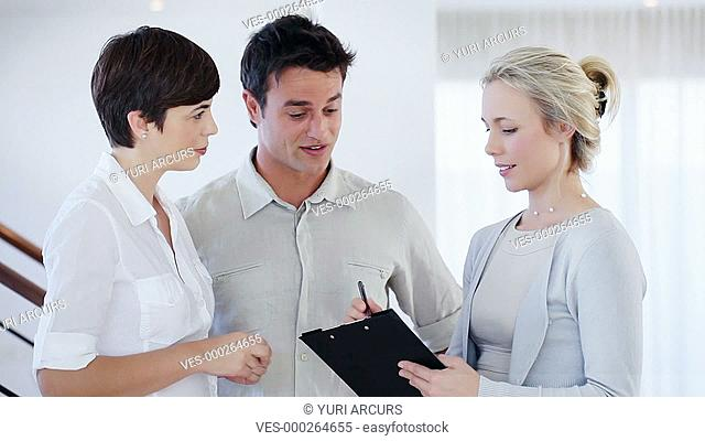 Young businesswoman holding a clipboard having a discussion with her two colleagues