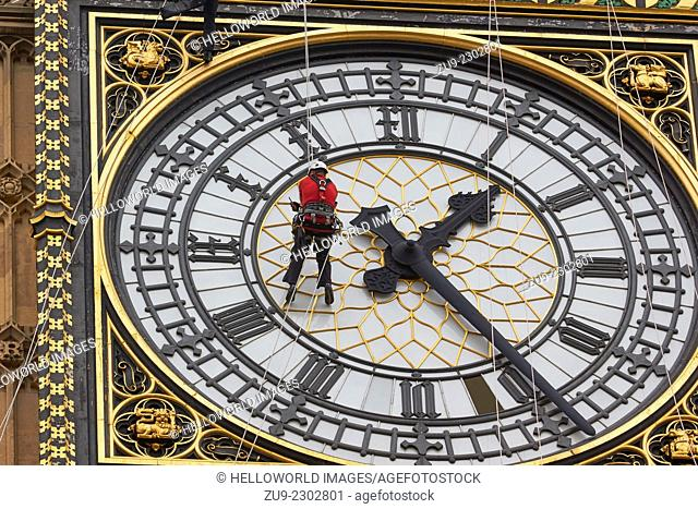 Worker suspended on ropes high above the ground cleaning the face of Big Ben clock tower, London, England, Europe