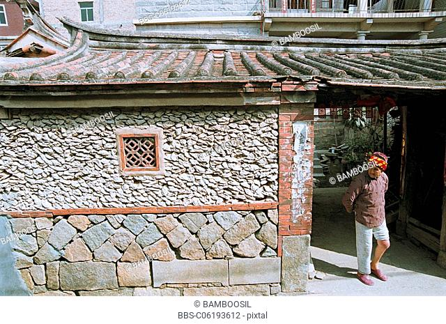 Xunpu woman standing by entrance of sea oyster shell house, Xunpu Village, Quanzhou City, Fujian Province of People's Republic of China