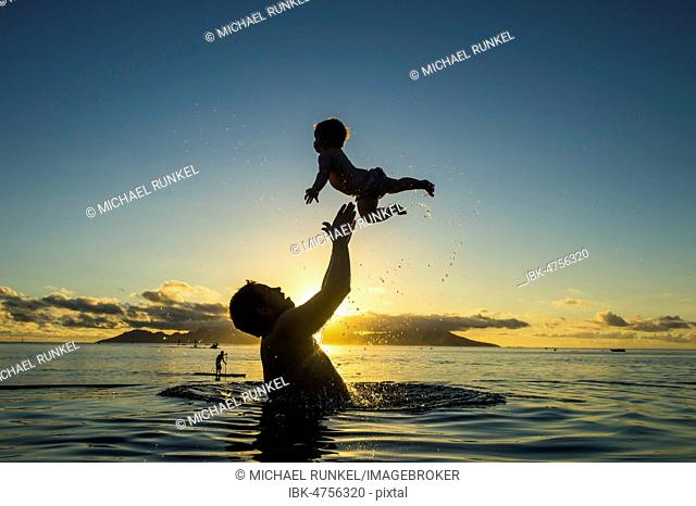 Father playing with his little baby in the water at sunset, Papeete, Tahiti