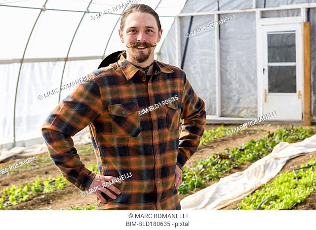 Caucasian farmer standing in greenhouse