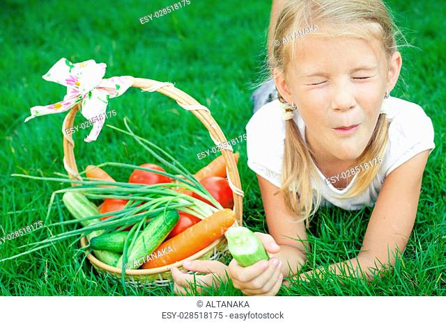 Happy little girl lying on the grass with a basket of vegetables at the day time. Concept of healthy food