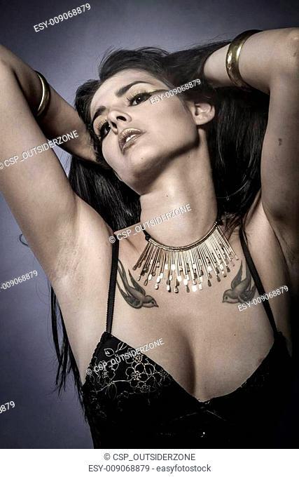 Sensual brunette dressed in black lingerie, golden jewelry