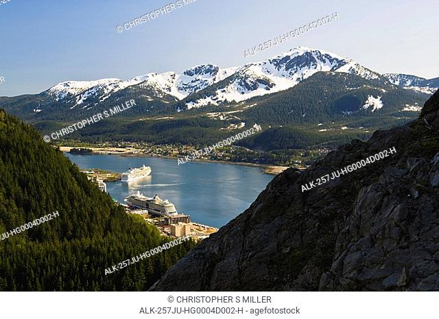 A hiker takes in the view of Gastineau Channel, Mt. Jumbo, and Downtown Juneau from the side of Mt. Roberts in Southeast Alaska during Summer