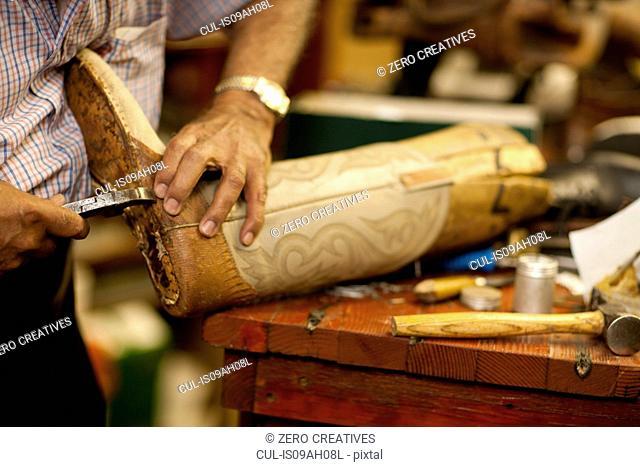 Cobbler mending sole of boot