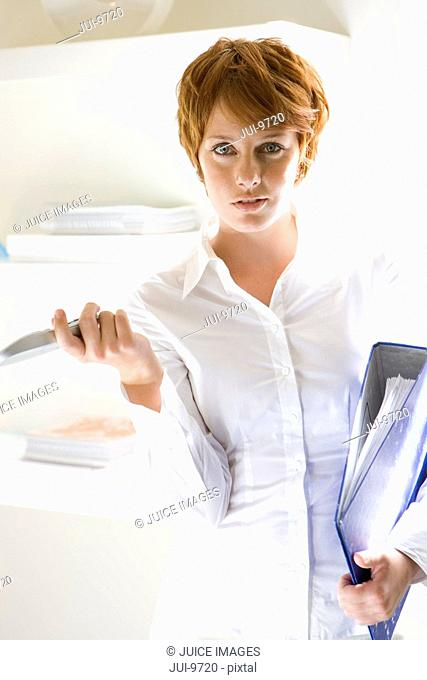 Businesswoman with folder and telephone, portrait