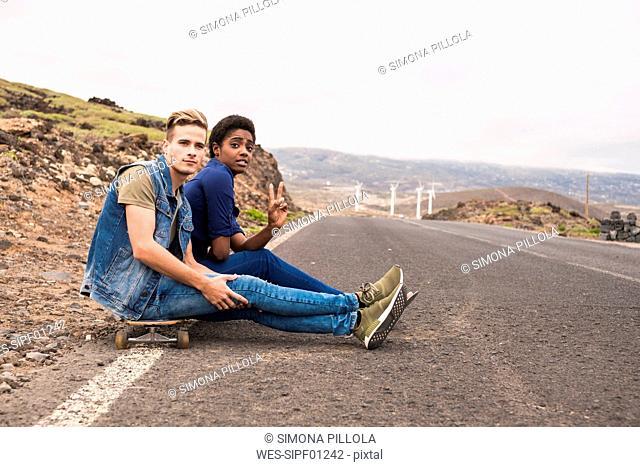 Spain, Tenerife, two friends with skateboard sitting at roadside