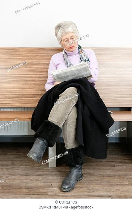 Woman reading a news paper, sitting on a bench in a waiting room with her coat on her lap and legs crossed