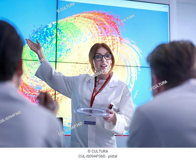 Female scientist making presentation in front of graphical display of silicon wafer on screens