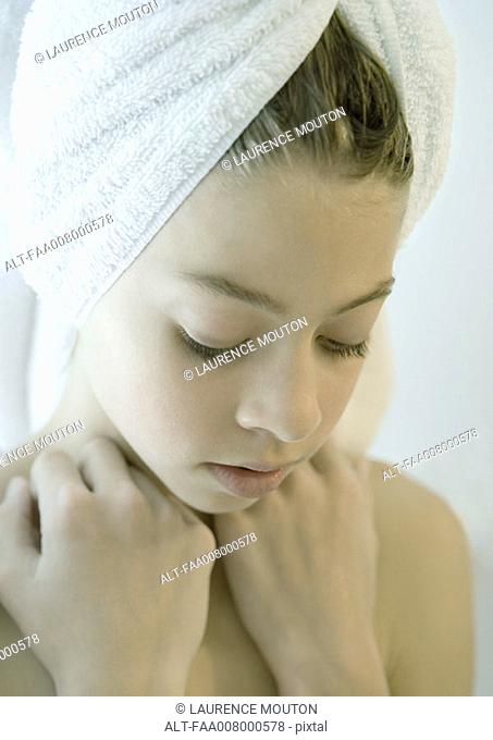 Girl with towel wrapped around hair, looking down