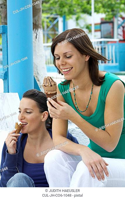 Two smiling women sitting on steps while eating ice cream