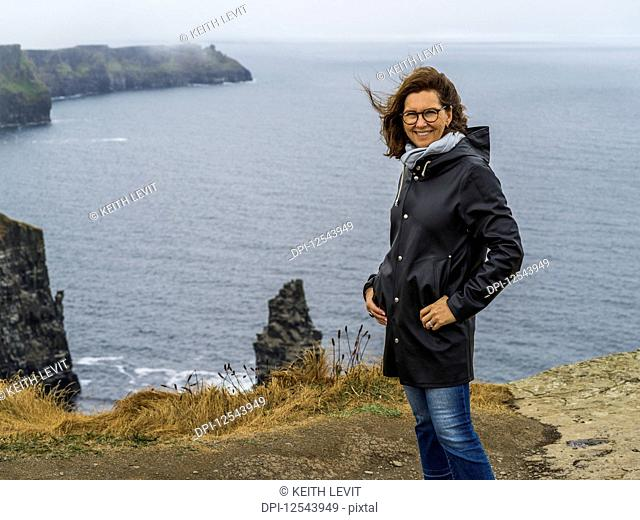 Portrait of a woman standing at the Cliffs of Moher; Ennistymon, County Clare, Ireland