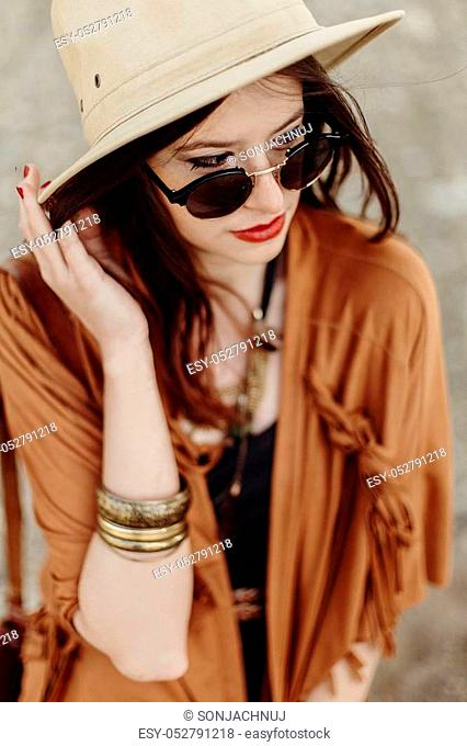 beautiful stylish boho woman in sunglasses and hat, fringe poncho and leather bag. hipster girl in gypsy look young traveler posing near river beach in...