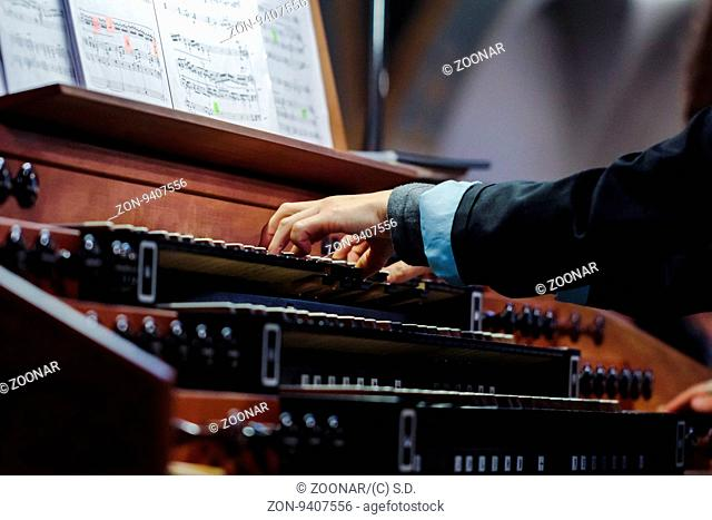 Organist playing a pipe organ, closeup view, with motion blur