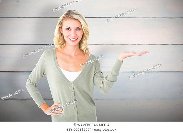 Composite image of pretty young blonde holding hand out