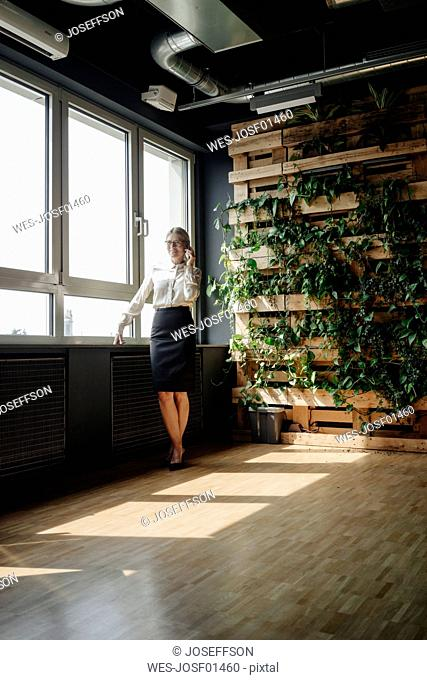 Businesswoman in green office on cell phone at the window