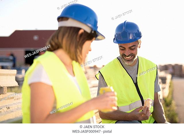 Construction workers eating sandwich sitting on stack of construction material