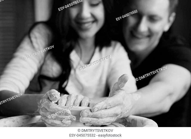 Pottery. Happy joyous romantic caucasian couple working together on potter's wheel and sculpting or making clay pot. Handsome man and beautiful pretty brunette...