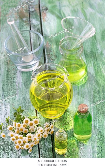 Chamomile oil and fresh chamomile flowers