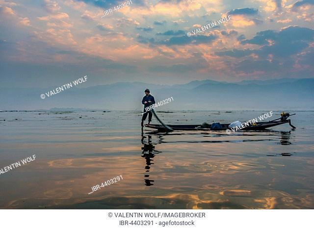 Local Intha fisherman rowing boat with one leg, unique local practice, sunrise, dawn, Inle Lake, Shan State, Myanmar