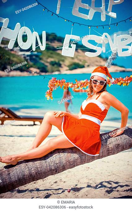 Cute woman in red dress, sunglasses and santa hat sitting on palm tree at exotic tropical beach. Holiday concept. Koh Samui, Thailand