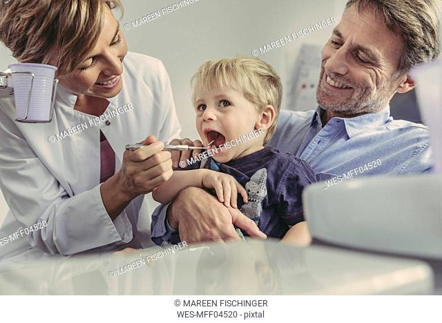 Female dentist examining little boy, sitting on his father's lap
