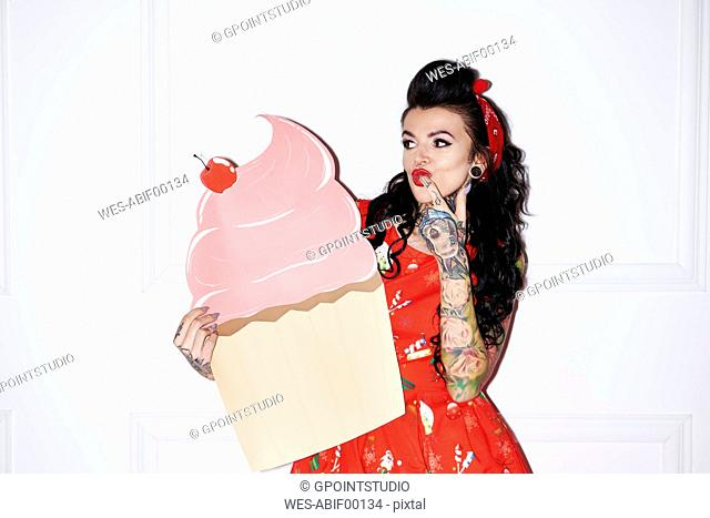 Portrait of tattooed woman with oversized cup cake