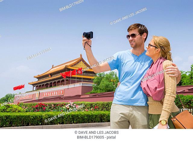 Caucasian couple taking selfie at historical building, Beijing, Beijing Municipality, China