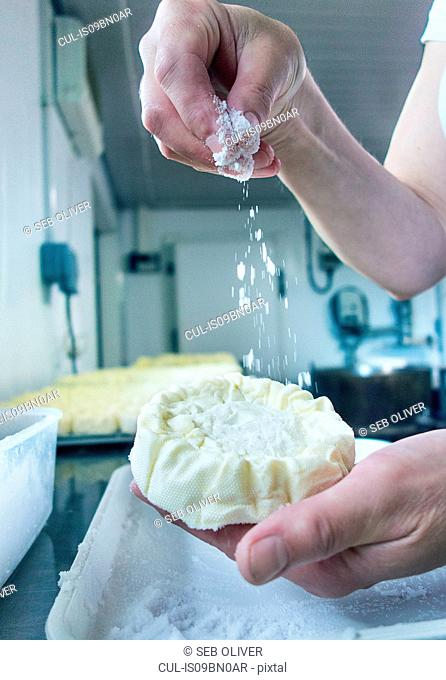 Female cheesemaker sprinkling cheese, close up of hands