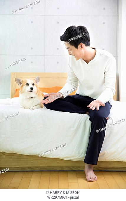 Young smiling bachelor playing with his pet dog