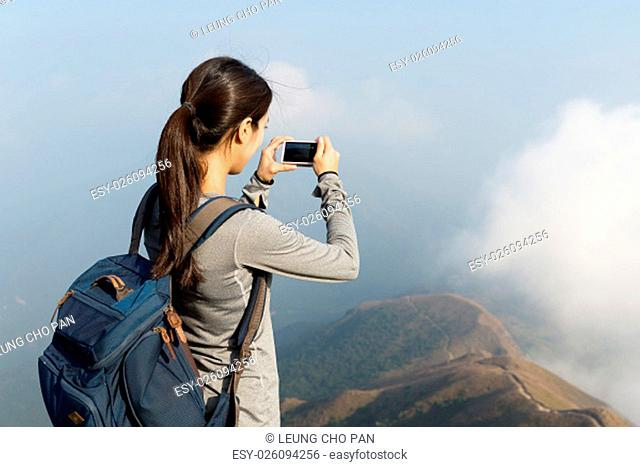 Woman taking photo at the top of the hill