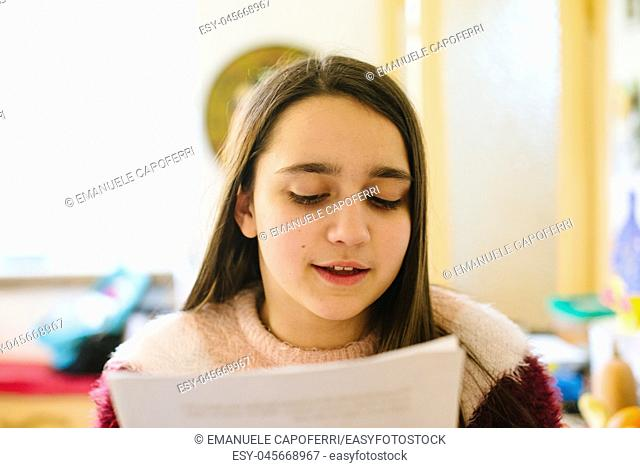 little girl, teen ager reads the papers she holds in her hand, studies for questioning school-close-up