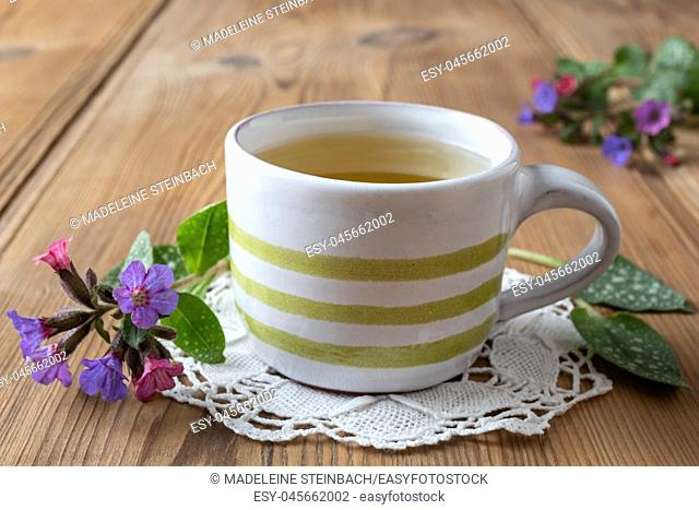A cup of herbal tea with fresh lungwort, or pulmonaria flowers