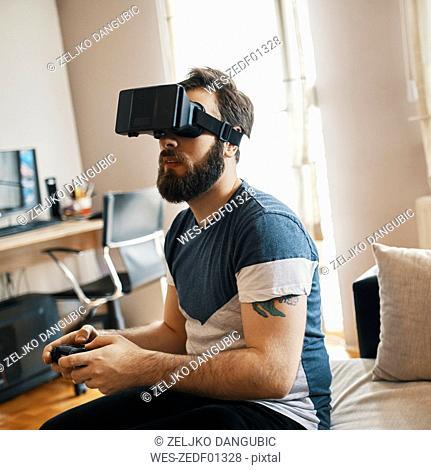 Man wearing virtual reality glasses at home playing computer game