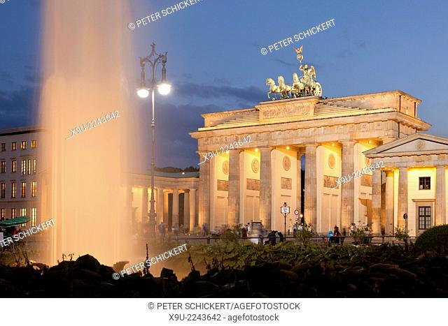 the illuminated Brandenburg Gate and fountain on Pariser Platz in Berlin, Germany, Europe