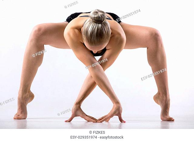 Sporty beautiful young woman practicing yoga, bending in variation of Goddess, Temple or Sumo Squat Pose, working out wearing black sportswear