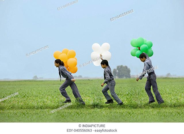 School students holding colored balloons