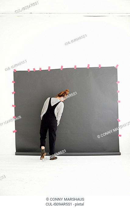 Woman in front of photographers backdrop, rear view