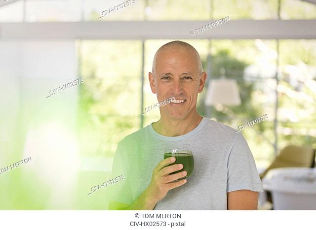 Portrait smiling mature man drinking healthy green smoothie