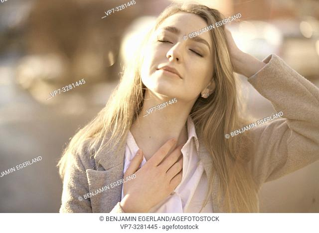 young woman outdoors with closed eyes enjoying sunlight, in Cottbus, Brandenburg, Germany