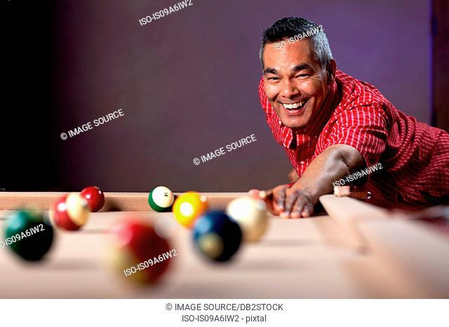 Smiling man playing pool