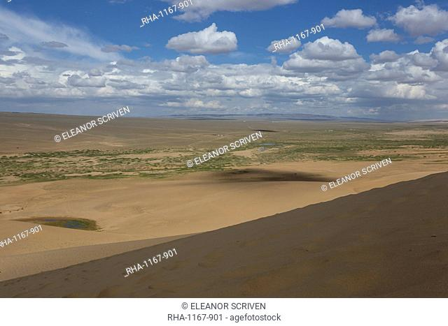 View down a huge sand dune towards a ger dotted plain and distant hills on a summer evening, Khongoryn Els, Gobi Desert, Mongolia, Central Asia, Asia