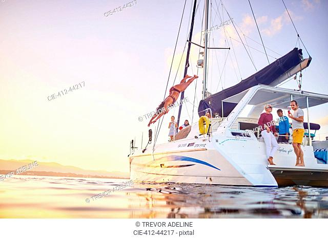 Young woman diving off catamaran into ocean