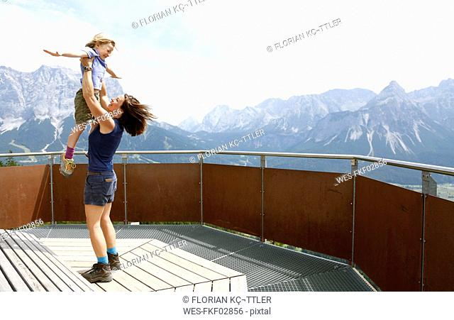 Austria, South Tyrol, mother lifting up her daughter