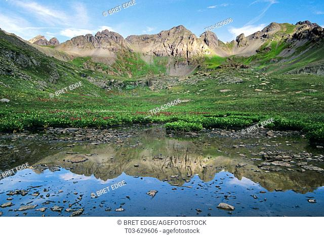 A tarn just below Clear Lake catches the reflections of a jagged mountain ridge high in the San Juans, Colorado, USA