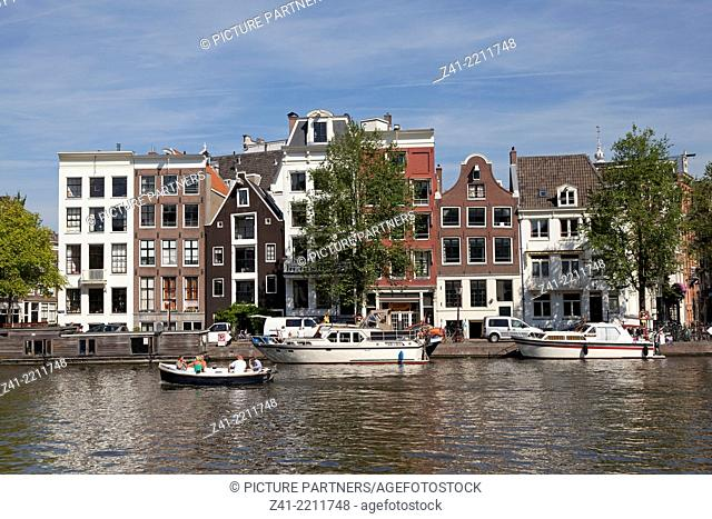 Boating in a canal in Amsterdam with facades of Dutch townhouses